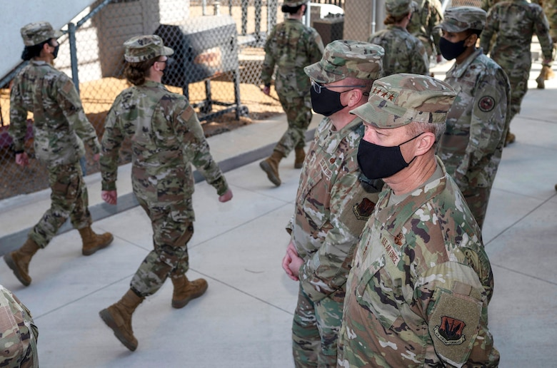 Basic trainees in uniform march in front of leadership.
