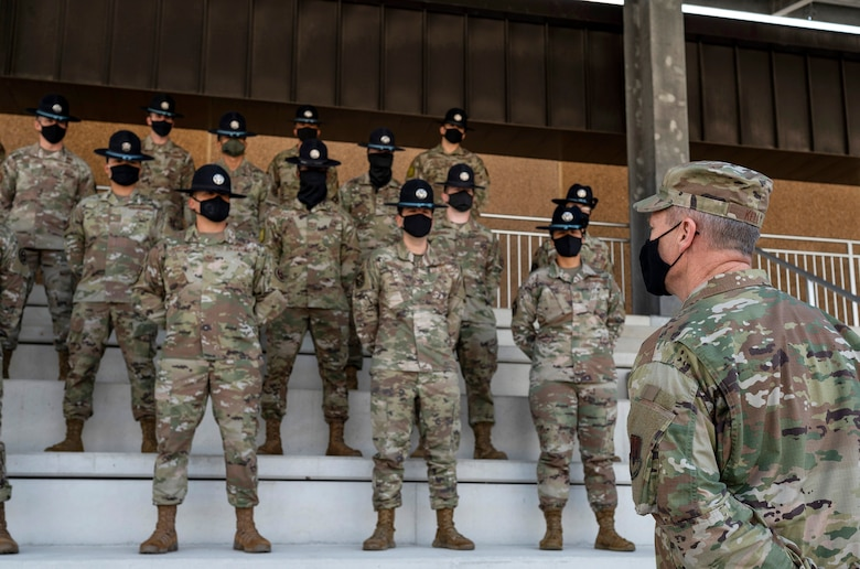 Military Training Instructors stand on bleachers in front of general in uniform.