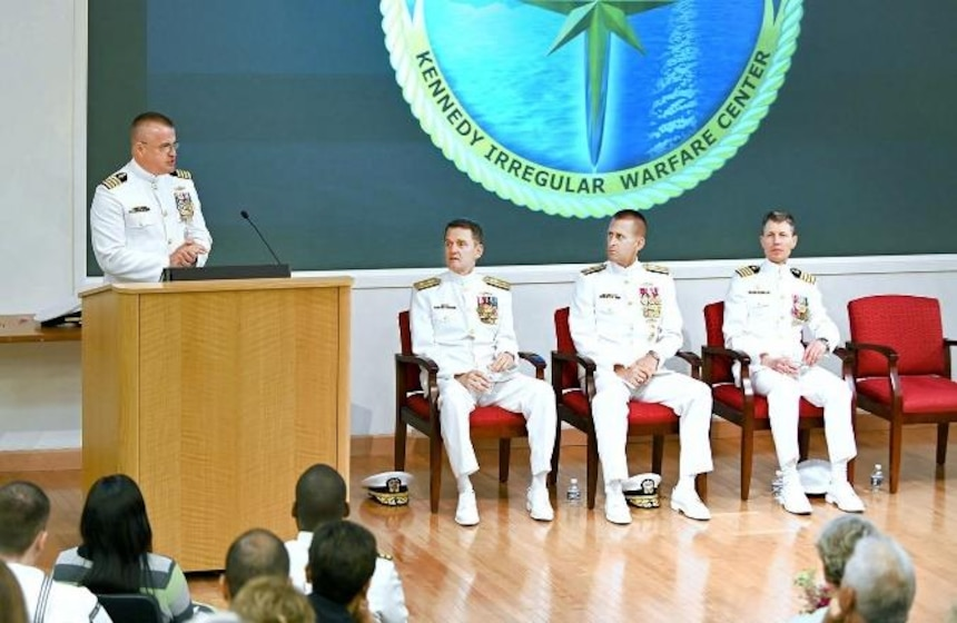 Capt. Charles (left) speaks to the audience during the Kennedy ceremony. Also picture d are ONI Commander Rear Adm. Price and Rear Adm. Okon