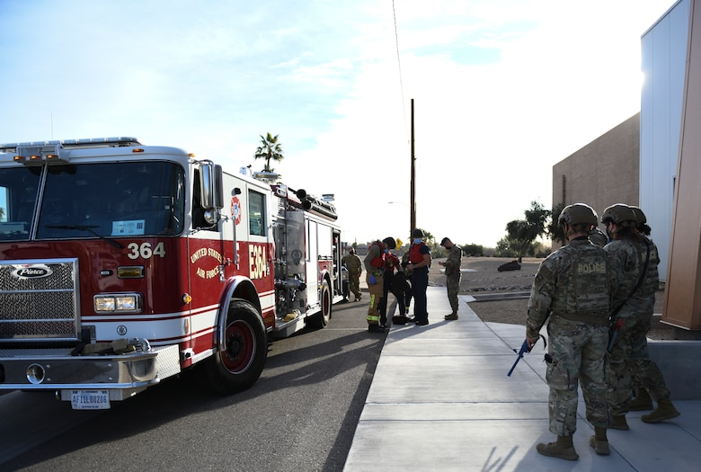 Airmen from the 56th Security Forces Squadron and the 56th Civil Engineer Squadron arrive on the scene of an active shooter exercise Feb. 26, 2021, at Luke Air Force Base, Arizona. Security forces escorted the firefighters into the area in play during the exercise, which evaluated the training, readiness and capability of Luke Airmen to respond to an active shooter. Exercises ensure Airmen meet warfighting needs with a continuous drive toward more effective and efficient training. (U.S. Air Force photo by Staff Sgt. Amber Carter)