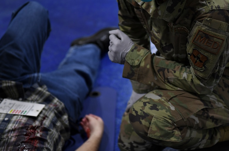 An Airman from the 56th Operational Medical Readiness Squadron provides medical care to a simulated victim during an active shooter exercise Feb. 26, 2021, at Luke Air Force Base, Arizona. Exercise evaluators assessed the training, readiness and capability of Luke Airmen to respond to an active shooter threat on the installation. Exercises ensure Airmen meet warfighting needs with a continuous drive toward more effective and efficient training. (U.S. Air Force photo by Staff Sgt. Amber Carter)