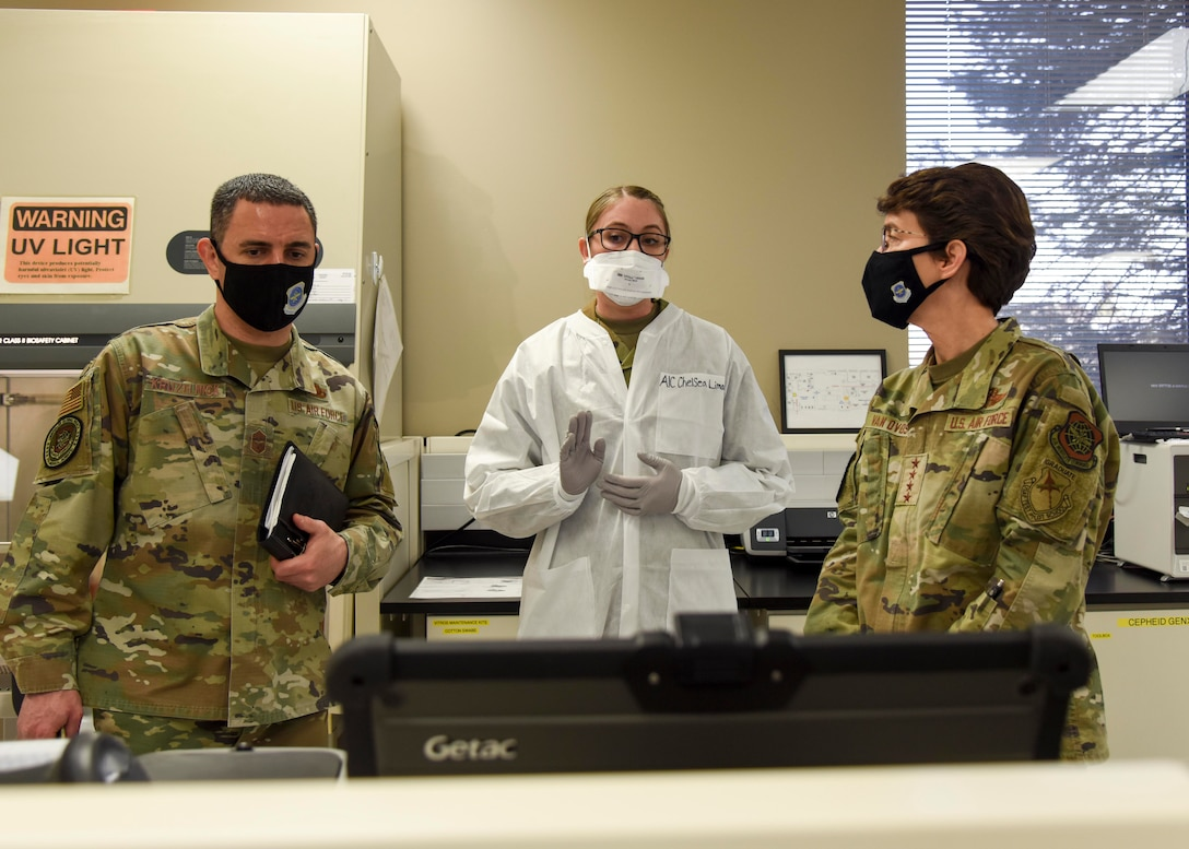 U.S. Air Force Airman 1st Class Chelsea Limacher, 92nd Medical Group laboratory technician, shows Gen. Jacqueline Van Ovost, Air Mobility Command commander and Chief Master Sgt. Brian Kruzelnick, AMC command chief, the Coronavirus-19 processing lab at Fairchild Air Force Base, Washington, March 4, 2021. The AMC command team learned how to perform a COVID-19 swab, run the test and interpret and communicate the results.  (U.S. Air Force photo by Airman 1st Class Anneliese Kaiser)