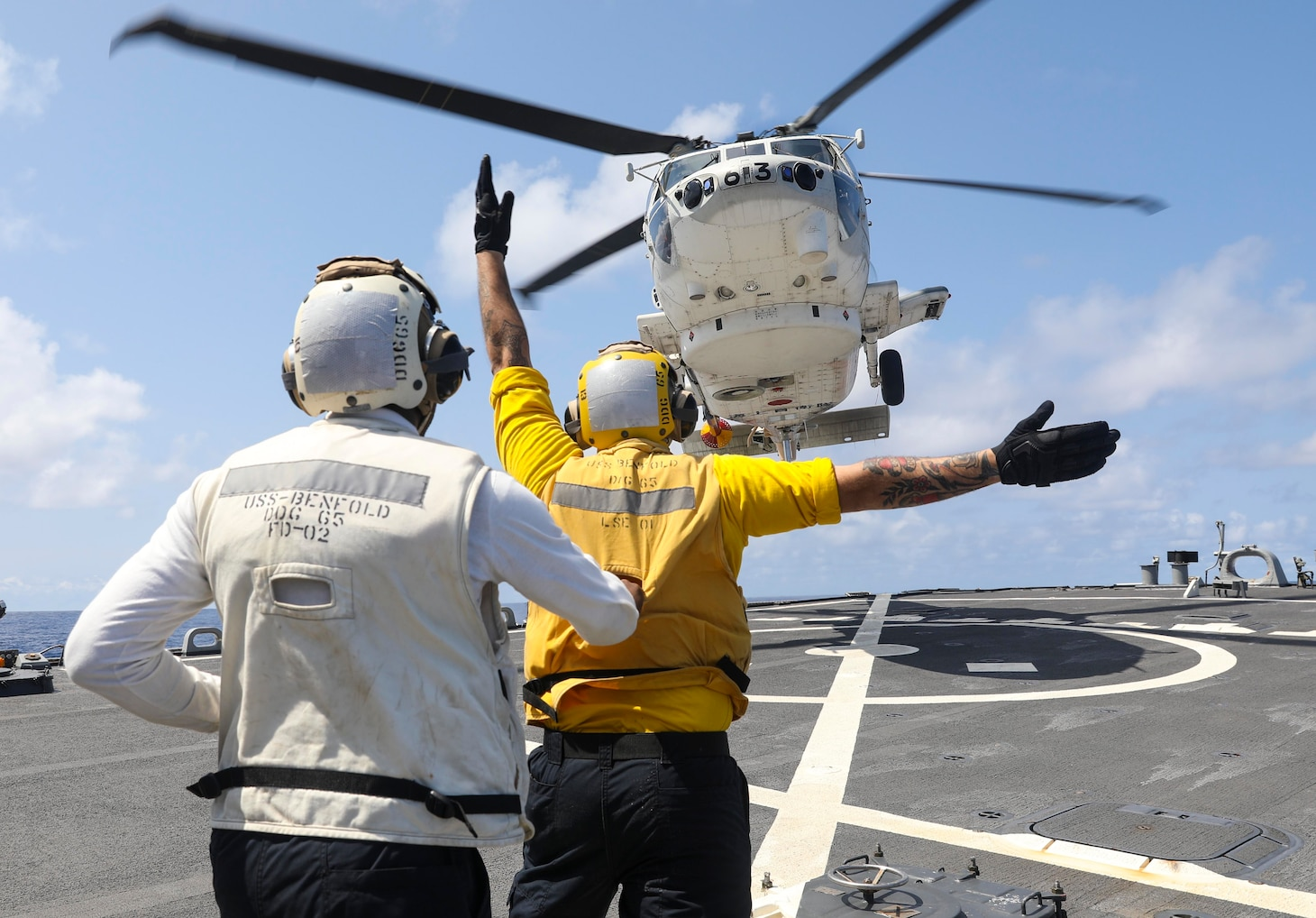 210304-N-FO714-2023 PHILIPPINE SEA (March 4, 2021) - Boatswain's Mate 2nd Class Dane Potzinger, from Ada, Mich., signals a Japan Maritime Self Defense Force SH-60 Seahawk to land on the flight deck of the Arleigh Burke-class guided-missile destroyer USS Benfold (DDG 65) while Boatswain's Mate 1st Class Glenrick Henry, from Bronx, N.Y., spots for safety during the annual U.S.-Japan Bilateral Advanced Warfighting Training Exercise. BAWT focuses on joint training and interoperability of coalition forces, and enables real-world proficiency and readiness in response to any contingency. (U.S. Navy photo by Mass Communication Specialist 2nd Class Deanna C. Gonzales)