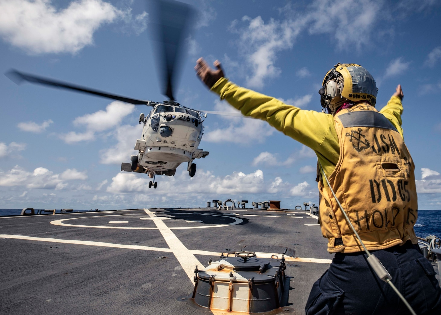 210304-N-HI376-1163 PHILIPPINE SEA (March 4, 2021) -  Boatswain's Mate 3rd Class Zachary Kai signals to a Japan Maritime Self-Defense Force (JMSDF) SH-60 Seahawk assigned to the JS Ise (DDH 182) on the flight deck of the Arleigh Burke-class guided-missile destroyer USS John S. McCain (DDG 56) during the annual U.S.-Japan Bilateral Advanced Warfighting Training exercise. BAWT focuses on joint training and interoperability of coalition forces, and enables real-world proficiency and readiness in response to any contingency. (U.S. Navy photo by Mass Communication Specialist 1st Class Jeremy Graham)