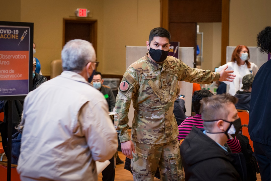 U.S. Air Force Capt. Aaron Sarwar, 118th Airlift Squadron navigator and site lead for Air National Guard personnel, directs patients to stations at a COVID-19 vaccination site at Saint Francis Hospital, Hartford, Connecticut, March 4, 2021. A team of 11 Connecticut Air National Guardsmen provided non-medical administrative support at the site, which was set up to vaccinate 1,500 teachers and staff from Hartford Public Schools.
