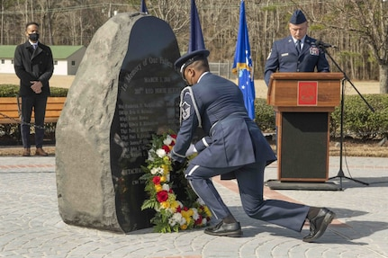 An honor guard Airman lays a wreath in front of a memorial