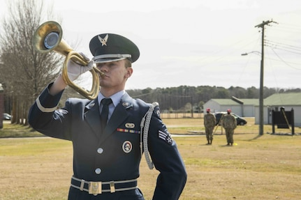 An Honor Guard Airman plays Taps on the trumpet