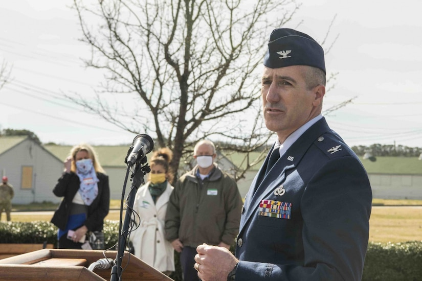 A U.S. Air Force colonel speaks to a crowd at the podium