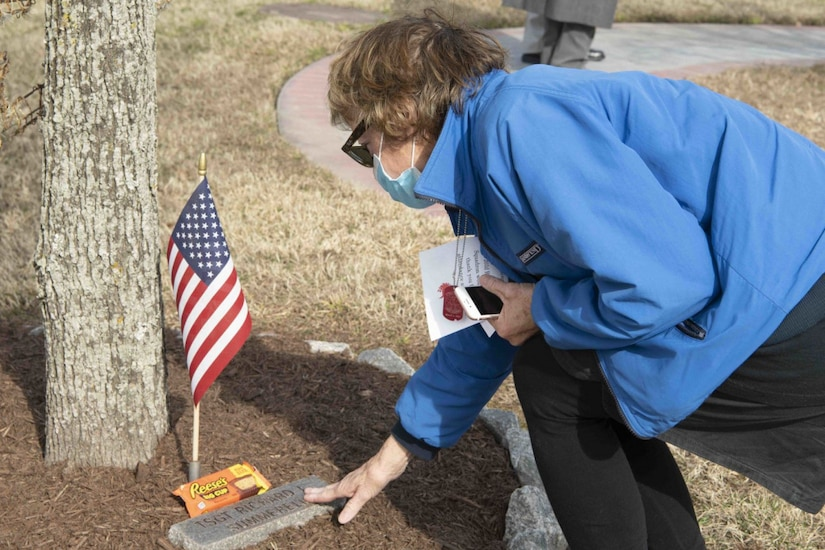A woman touches a plaque in the ground under a tree