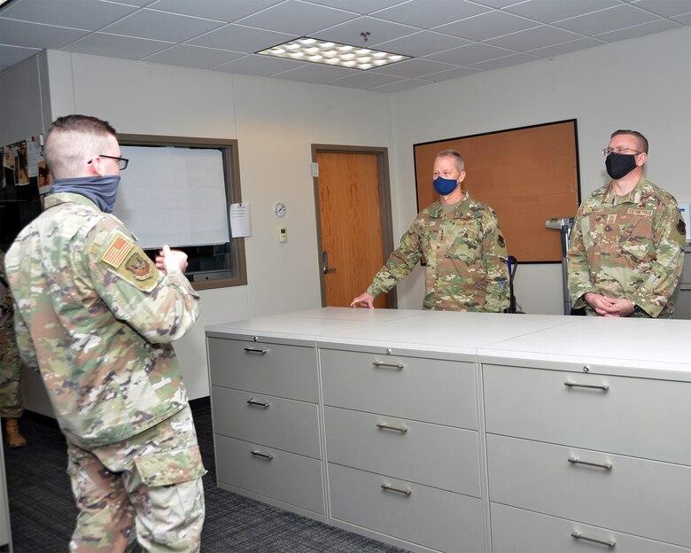 An officer in uniform briefs leadership in uniform in a room.