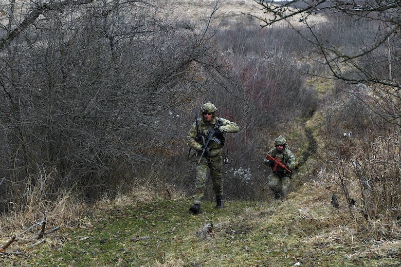 Two pararescuemen with the 57th Rescue Squadron search for a downed pilot during Operation Porcupine in Romania, March 4, 2021.