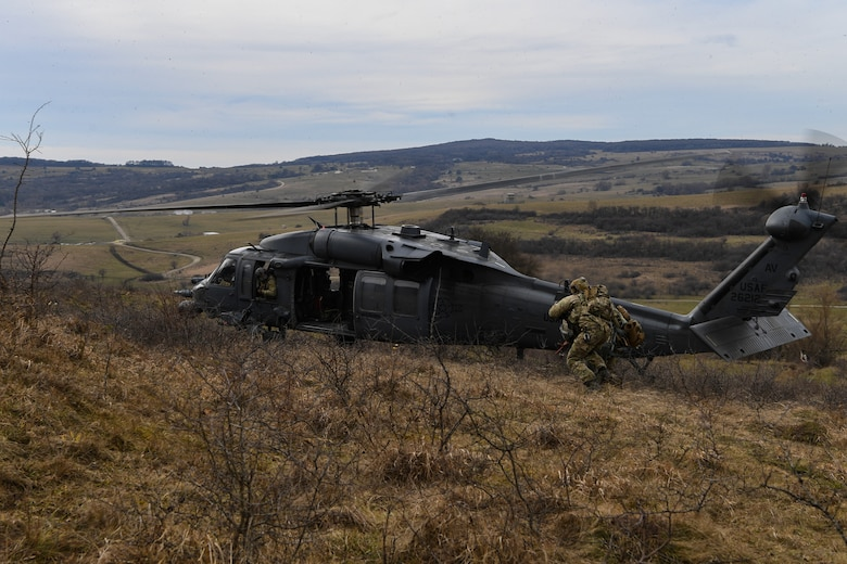Two pararescuemen escort a downed pilot to a U.S. Air Force HH-60G Pave Hawk helicopter during Operation Porcupine in Romania, March 4, 2021.