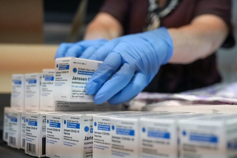 Someone wearing gloves holds a box of the first doses of the Johnson and Johnson vaccines.