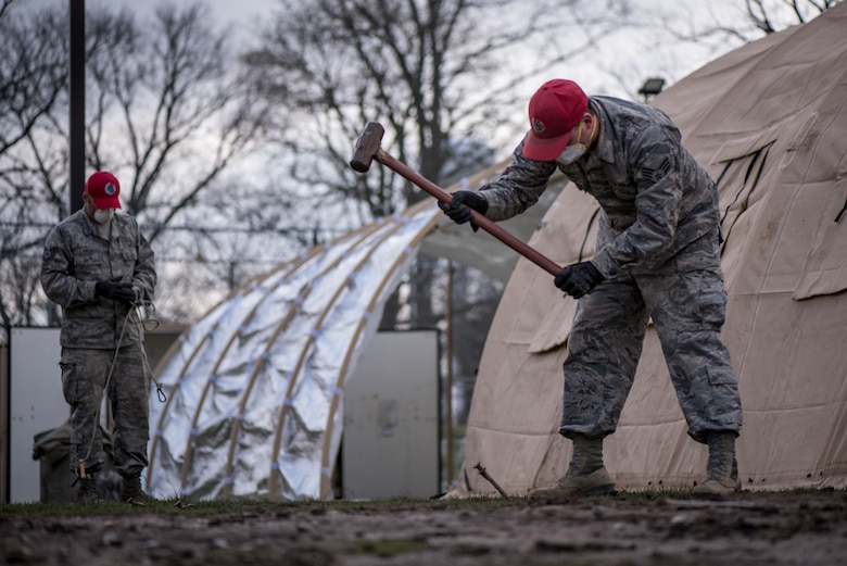 Senior Airman Michael Hyer stakes a tent down while working with Ohio National Guard members supporting the Ohio Department of Rehabilitation and Correction in response to confirmed COVID-19 cases at the Pickaway Correctional Institution, Orient, Ohio.