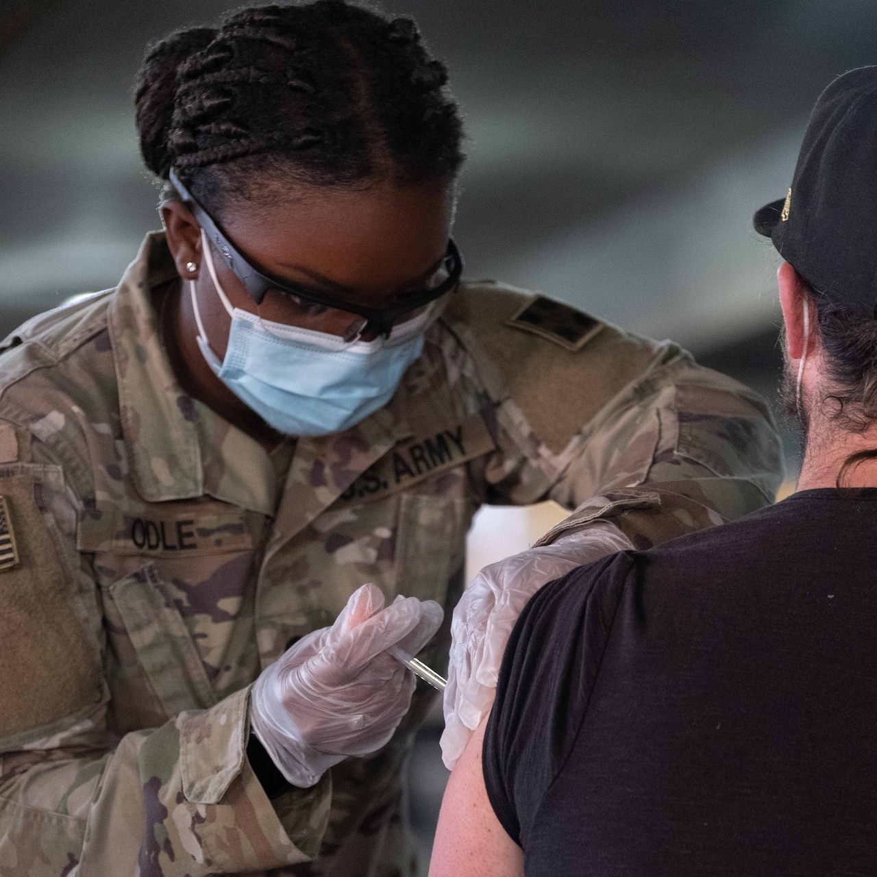 A woman in a military uniform injects a vaccine into the arm of a civilian.