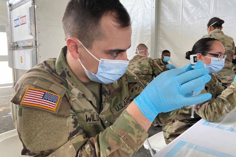 A man in a military uniform fills a syringe with a vaccine.
