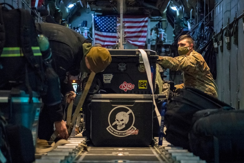 Airmen load a C-130 and strap cargo down