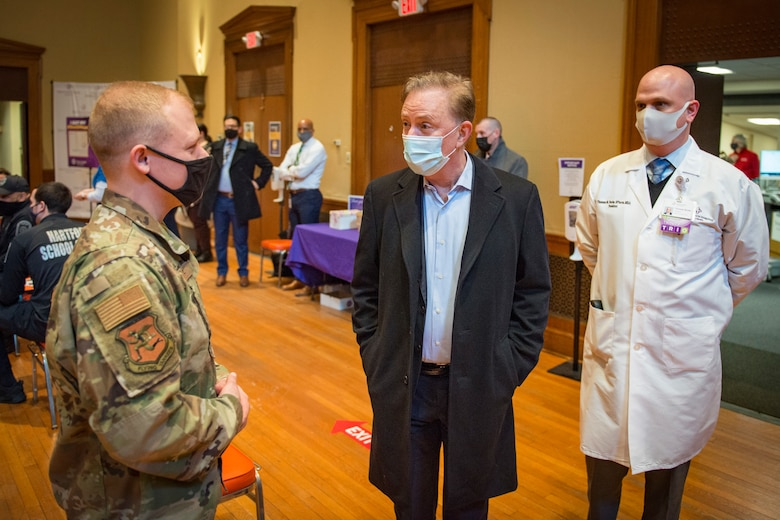 Connecticut Gov. Ned Lamont and Thomas Burke, Saint Francis Hospital President, meet with U.S. Air Force Staff Sgt. Christopher Brule, 103rd Maintenance Squadron aerospace ground equipment specialist, at a COVID-19 vaccination site at Saint Francis Hospital, Hartford, Connecticut, March 4, 2021. A team of 11 Connecticut Air National Guardsmen provided non-medical administrative support at the site, which was set up to vaccinate 1,500 teachers and staff from Hartford Public Schools. (U.S. Air National Guard photo by Staff Sgt. Steven Tucker)