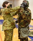 Tech. Sgt. Ellie Drake, 931st Civil Engineer Squadron Emergency Management technician, assists a McConnell Reservist with their M50 gas mask during a Chemical, Biological, Radiological and Nuclear survival skills training March 5, 2020, at McConnell Air Force Base, Kansas.