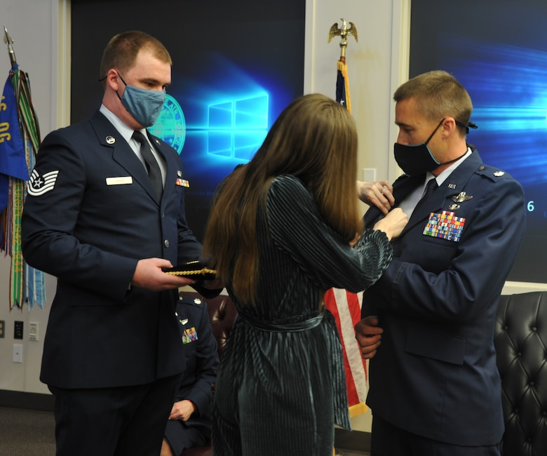 Lt. Col Daniel Arneson receives commander's pin from his wife, Heather, after becoming the new commander of the 728th Airlift Squadron during a change of command ceremony at Joint Base Lewis-McChord, Washington, March 6, 2021.