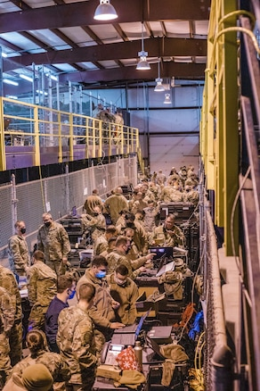 Military members work on communication equipment.