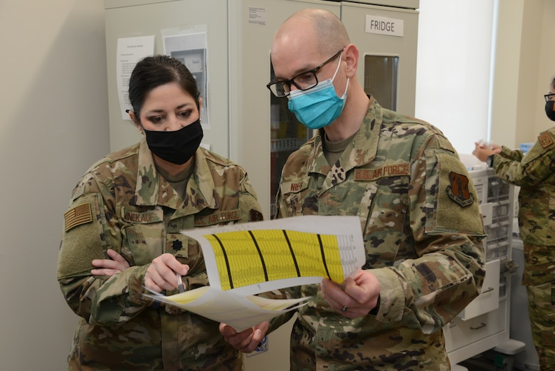 Lt. Col. Tonja Winekauf and Capt. Paul Niles look over a list of patients who are scheduled to receive COVID vaccinations.