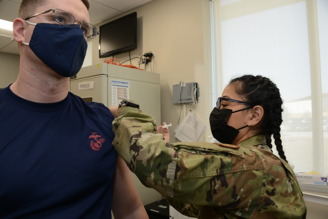 U.S. Marine Corps recruiter Staff Sgt. Jason Homard receives a COVID-19 vaccination.
