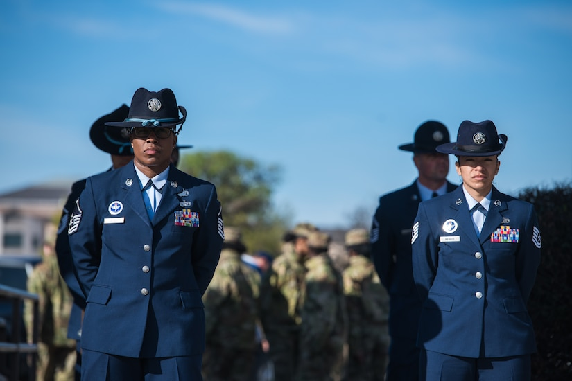 Training instructors stand at parade rest.