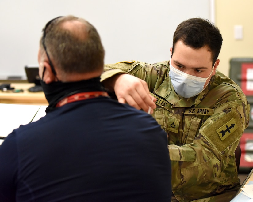 A Soldier with the Michigan Amy National Guard serving with Michigan National Guard's COVID-19 Vaccination Testing Team administers a COVID-19 vaccination in Augusta, Michigan, March 3, 2021. The Michigan Army and Air National Guard hosted a vaccination clinic for service members and Department of Defense personnel at Fort Custer Training Center.