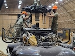 Two soldiers in camo uniforms and orange hard hats stand on top of a helicopter part to perform maintenance.