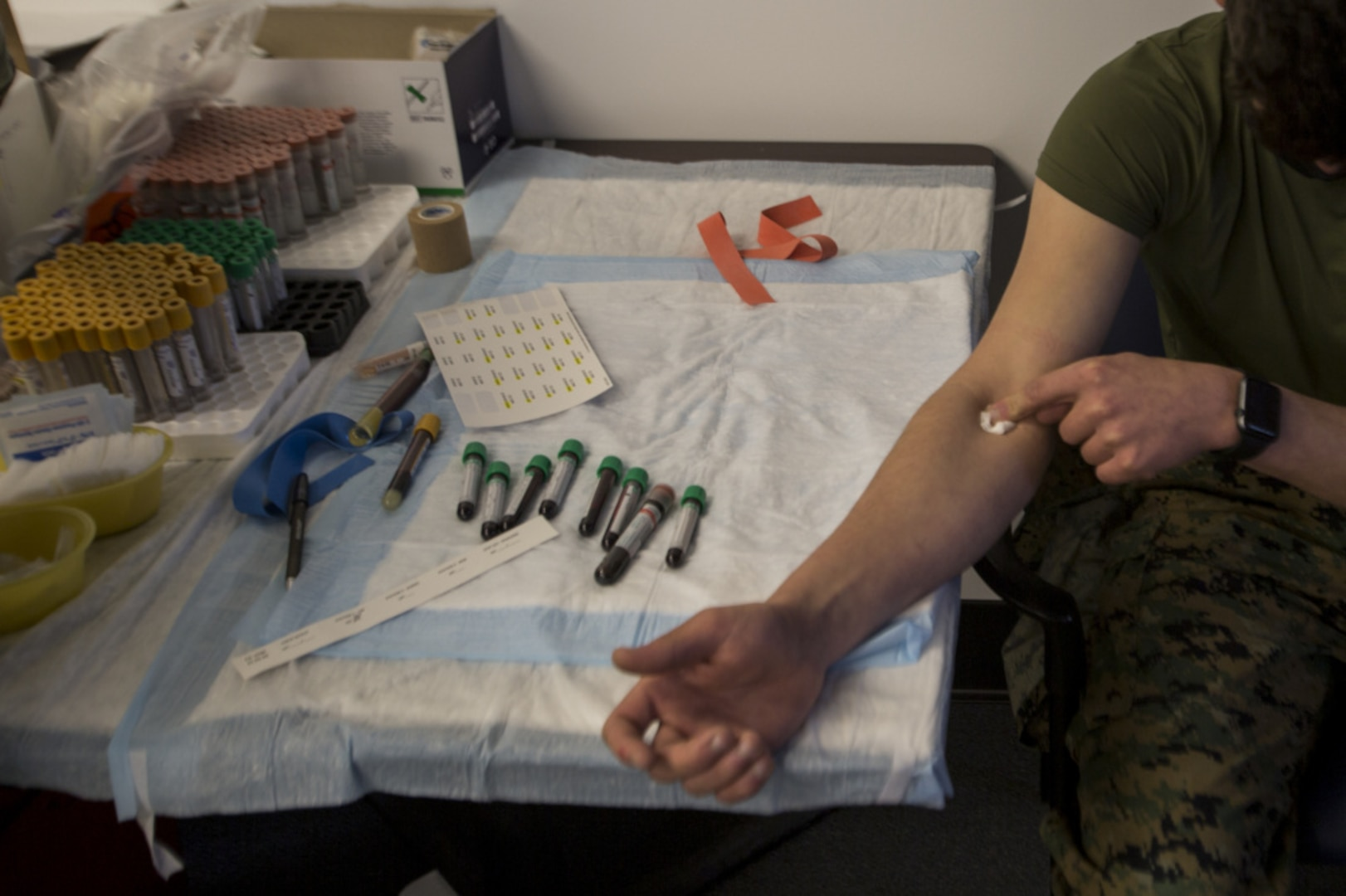 A U.S. Marine participant with the COVID-19 Health Action Response for Marines (CHARM) study covers a needle hole after getting his blood sample collected on Camp Johnson, N.C., Mar. 3, 2021.