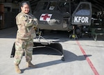 Pfc. Genevieve Godgow, an aircraft structural repairer attached to 3rd Battalion, 238th General Support Aviation Battalion, Delaware Army National Guard, smiles for a picture in front of a UH-60 Blackhawk at Camp Bondsteel, Kosovo, on March 3, 2021.