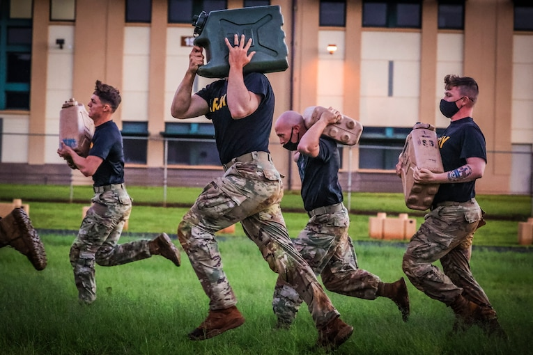 Soldiers run while carrying an object.