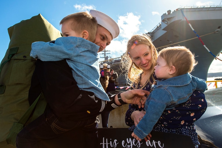 A sailor greets his family on a pier.