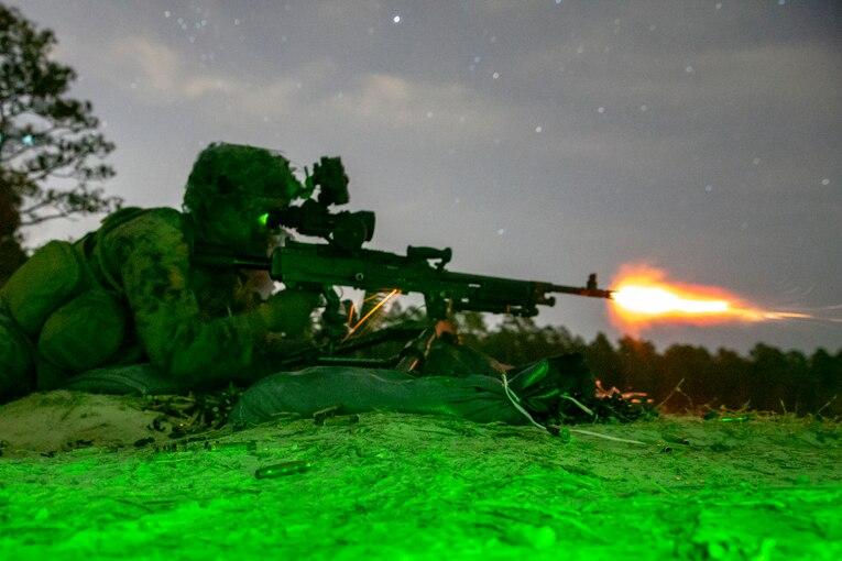 A Marine fires his machine gun at night under a green light.