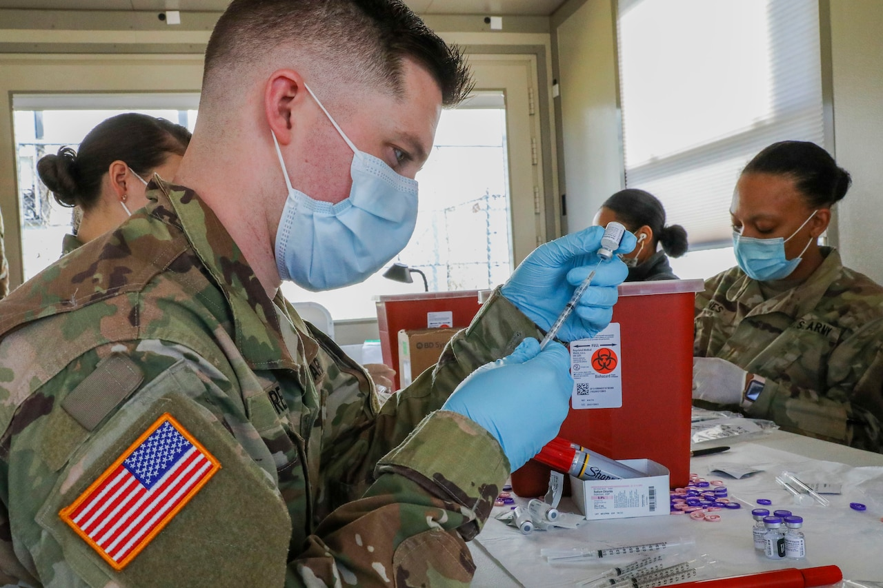 Four soldiers wearing face masks and gloves prepare syringes for COVID-19 vaccines.