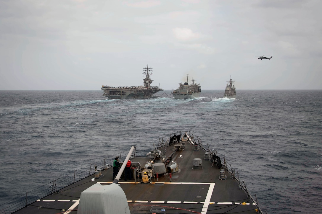 Ships sail in formation as helicopter hovers above as seen from the deck of another ship.