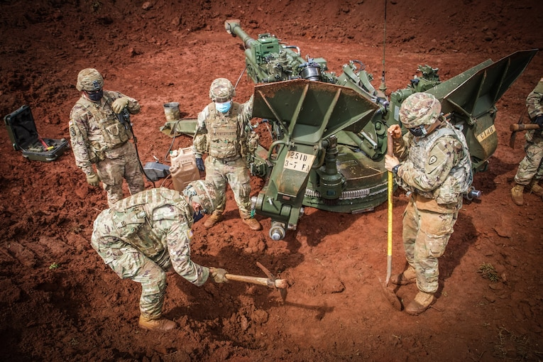 Four soldiers stand around a large gun and dig a hole in the ground.