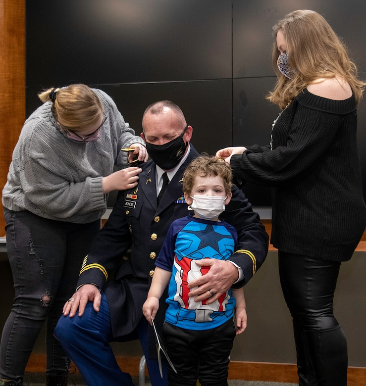 Newly promoted Col. Ronald W. Bonesz's daughter, Melanie (left), son Lucas (standing) and wife, Blair, place his new rank on during a promotion ceremony Feb. 26 at Camp Lincoln in Springfield, Illinois.