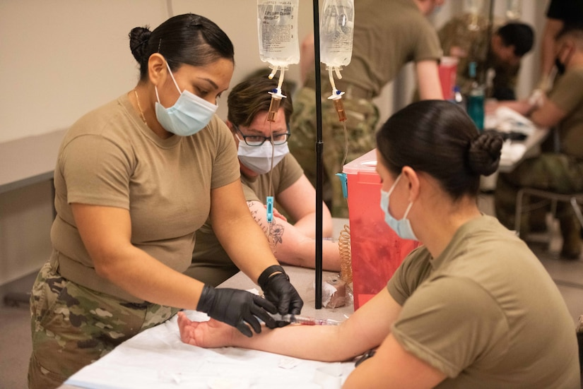 Three female soldiers practice a medical simulation.