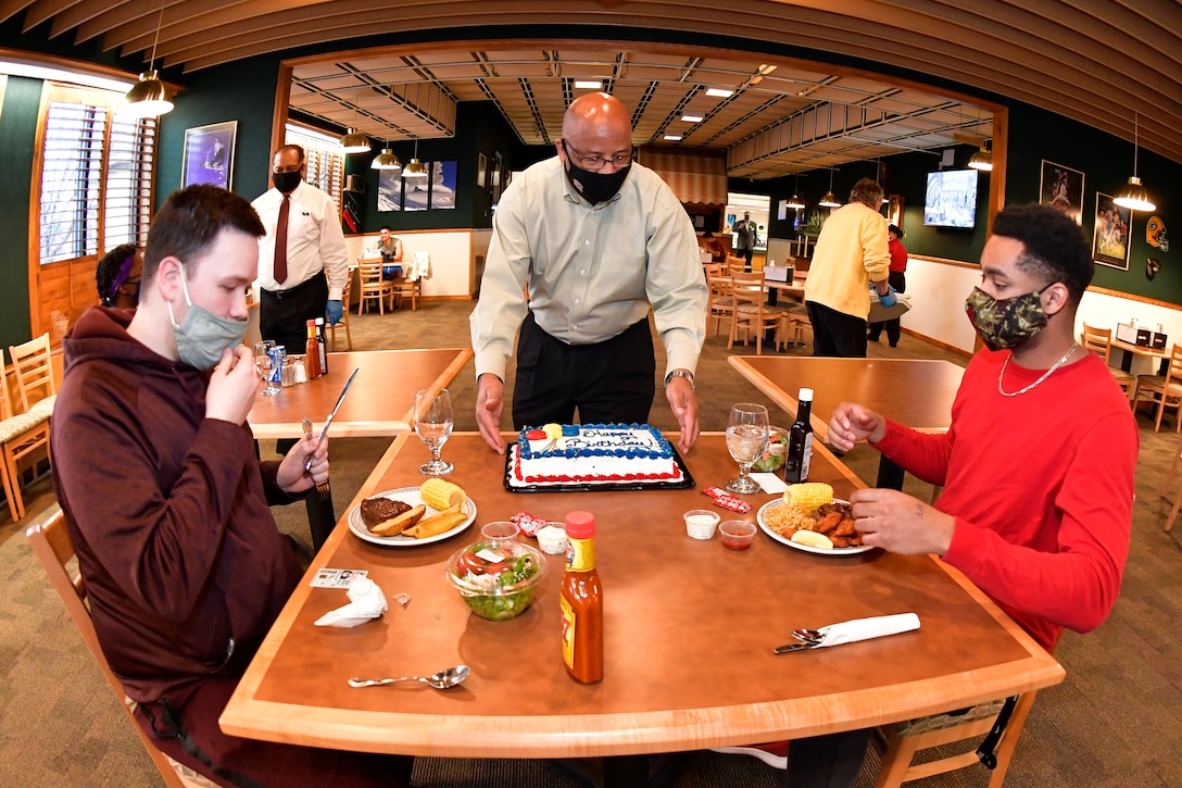 Airman 1st Class Dawson Sigetti (left) and Airman 1st Class John Moore, both with 75th Force Support Squadron, are served a birthday cake by Moses Thompson, 75th FSS Sustainment Flight chief, at the Hillcrest Dining Facility March 3, 2021, at Hill Air Force Base , Utah. A new birthday meal program was introduced to allow dorm residents and guest to celebrate by receiving a special no-cost birthday meal and cake at the dining facility. (U.S. Air Force photo by Todd Cromar)