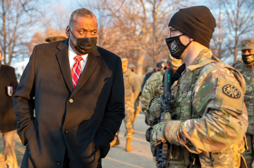 A man in a business suit speaks with a man in a military uniform.