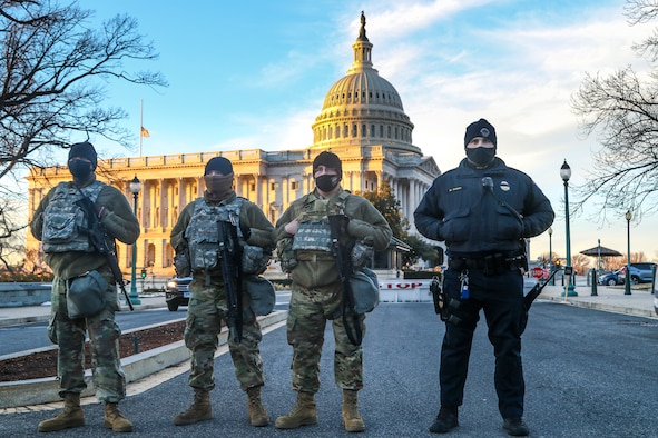 Three men in military uniforms and one man in a police uniform stand near each other in front of the U.S. Capitol.