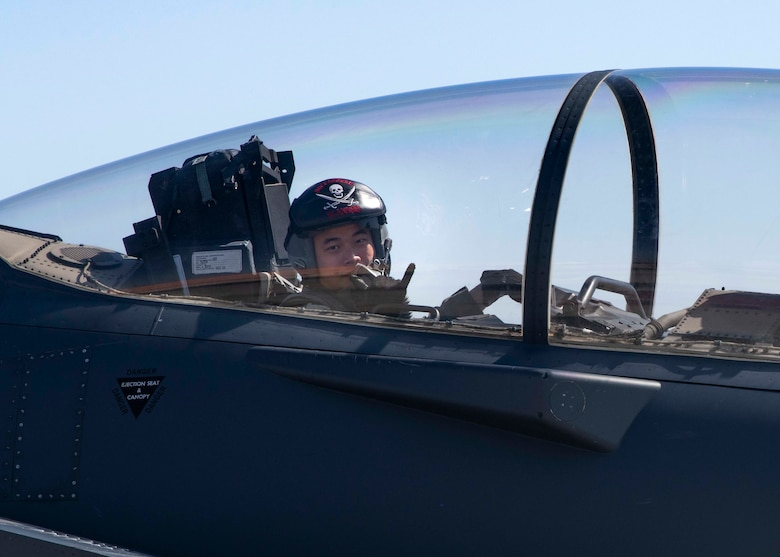 A weapons system operator from the 428th Fighter Squadron holds up a shaka hand symbol from the back seat of an F-15SG Strike Eagle.