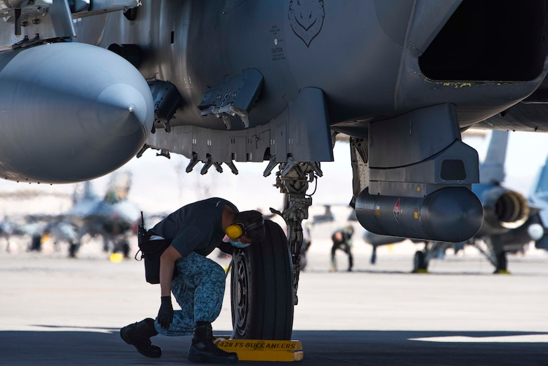 A crew chief from the 428th Fighter Squadron places chocks in front of an F-15SG Strike Eagle's tire.