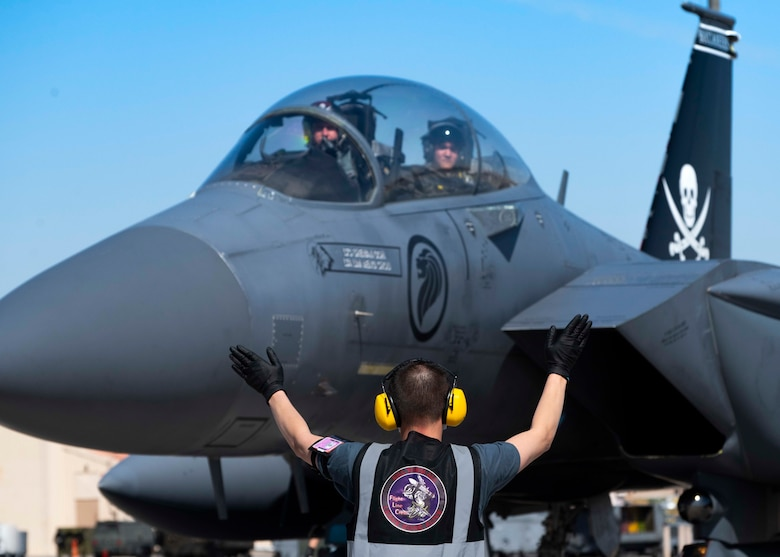 A crew chief from the 428th Fighter Squadron marshals an F-15SG Strike Eagle on the flightline.