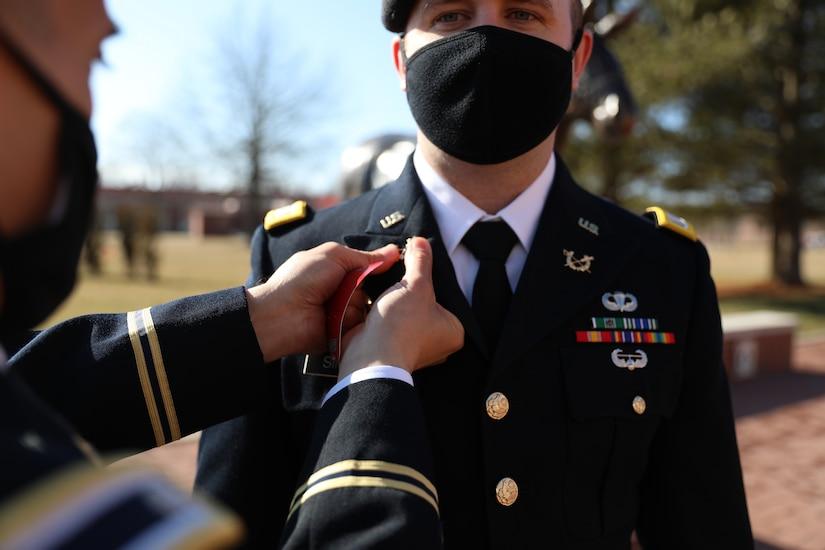 Male soldier in dress uniform pins branch insignia on male soldier in dress uniform.