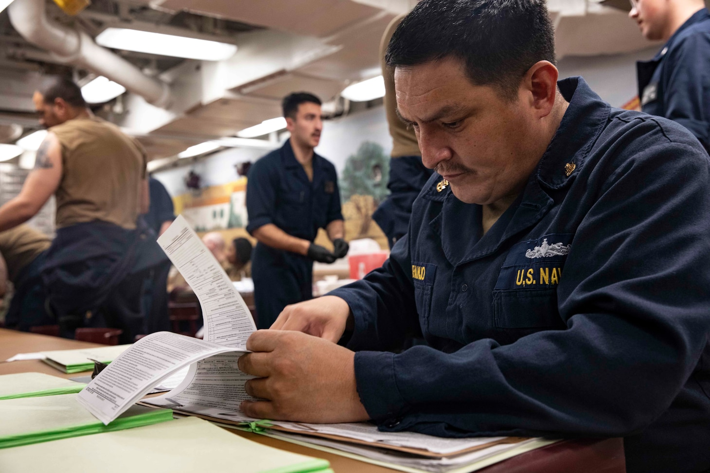 210220-N-BM428-0122 SOUDA BAY, Greece (Feb. 20, 2021) Senior Chief Hospital Corpsman Andre Naranjo verifies paperwork for Sailors aboard the Arleigh Burke-class guided-missile destroyer USS Porter (DDG 78) in roder for them to receive the COVID-19 vaccine in Souda Bay, Greece, Feb. 20, 2021. Porter, forward deployed to Rota, Spain, is on its ninth patrol in the U.S. Sixth Fleet area of operations in support of U.S. national interests and security in Europe and Africa. (U.S. Navy photo by Mass Communication Specialist 2nd Class Damon Grosvenor)