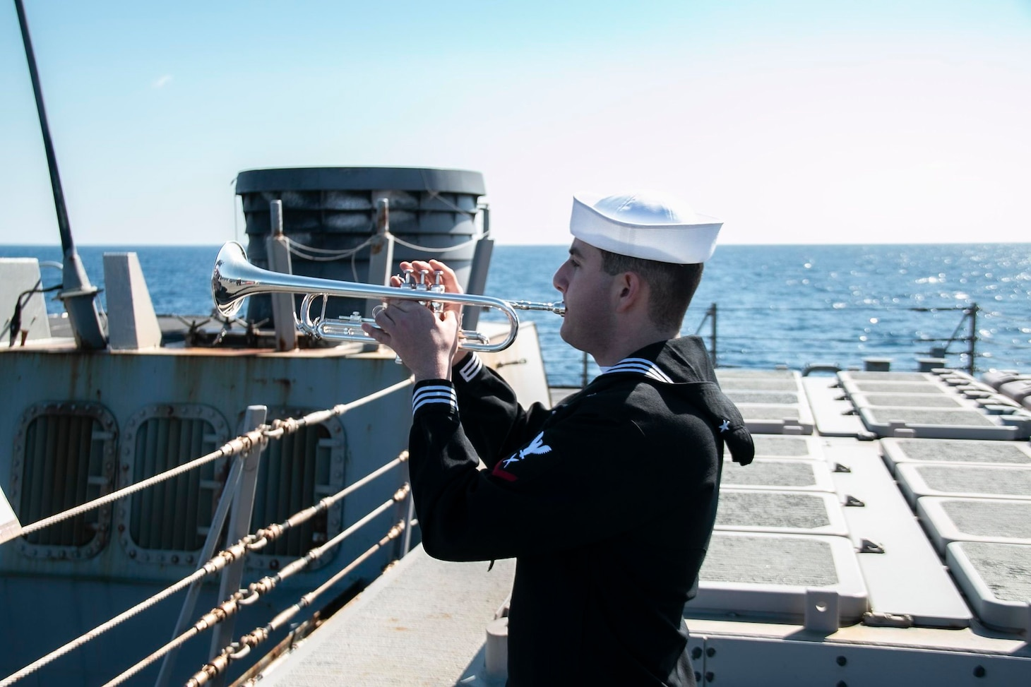 """210304-N-RG171-0337 MEDITERRANEAN SEA (Mar. 4, 2021) Yeoman 3rd Class Mark Martinez plays """"Taps"""" during a burial-at-sea aboard the Arleigh Burke-class guided-missile destroyer USS Donald Cook (DDG 75), Mar. 4, 2021. Donald Cook, forward-deployed to Rota, Spain, is on patrol in the U.S. Sixth Fleet area of operations in support of regional allies and partners and U.S. national security in Europe and Africa. (U.S. Navy photo by Machinist's Mate 1st Class Peter Stitzel/Released)"""