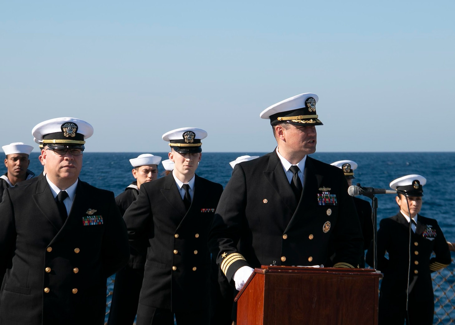 210304-N-RG171-0261 MEDITERRANEAN SEA (Mar. 4, 2021) Cmdr. Matthew Curnen, commanding officer of the Arleigh Burke-class guided-missile destroyer USS Donald Cook (DDG 75), front right, speaks during a burial-at-sea, Mar. 4, 2021. Donald Cook, forward-deployed to Rota, Spain, is on patrol in the U.S. Sixth Fleet area of operations in support of regional allies and partners and U.S. national security in Europe and Africa. (U.S. Navy photo by Machinist's Mate 1st Class Peter Stitzel/Released)